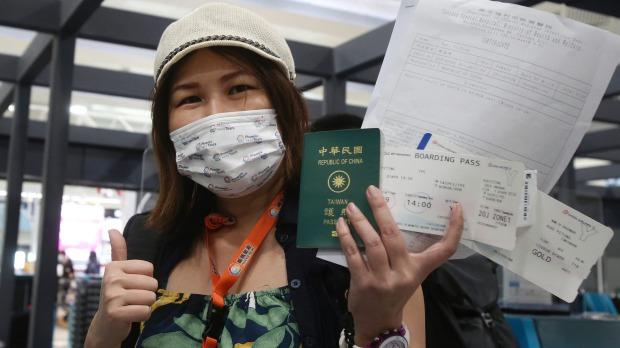 Kuo Yitting, uno de los primeros grupos en viajar a Palau, muestra su tarjeta de embarque y prueba de virus antes de salir de Taiwán el ...